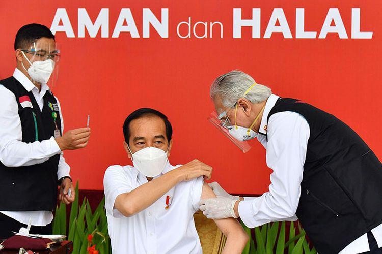 Presiden Joko Widodo (tengah) bersiap disuntik dosis pertama vaksin Covid-19 produksi Sinovac oleh vaksinator Wakil Ketua Dokter Kepresidenan Prof Abdul Mutalib (kanan) di beranda Istana Merdeka, Jakarta, Rabu (13/1/2021). Penyuntikan perdana vaksin Covid-19 ke Presiden Joko Widodo tersebut menandai dimulainya program vaksinasi di Indonesia.