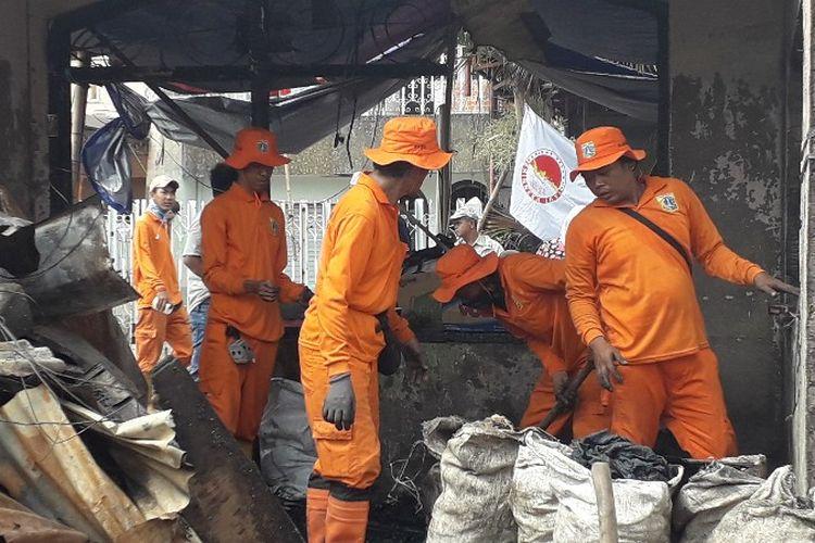 Petugas PPSU membersihkan sampah-sampah bekas kebakaran di Jalan Perumahan Taman Kota, RT 16 RW 05, Kebakatan Utara, Kebakaran, Jakarta Barat pada Senin (2/4/2018).