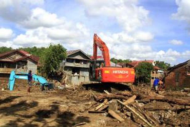 Alat berat terlihat masih bekerja mengangkat sampah dan material lumpur yang ditinggalkan paska banjir bandang melanda Manado.