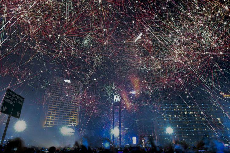 Suasana pesta kembang api saat malam tahun baru 2018 di kawasan Bundaran HI, Jakarta, Senin (1/1/2018). Sejumlah warga ibukota dan sekitarnya memadati kawasan itu untuk merayakan malam pergantian tahun 2017 ke 2018.