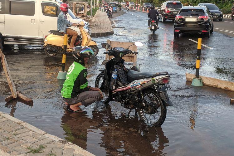 warga bergantian memanfaatkan semburan air di Jalan Boulevard BGR Perintis Kemerdekaan, Kelapa Gading Barat, Jakarta Utara, Selasa (21/1/2020)