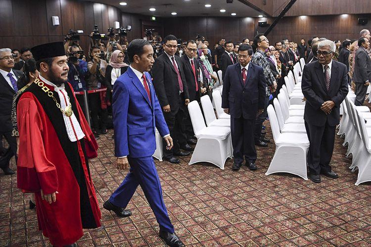 Presiden Joko Widodo (kedua kiri) bersama Ketua Mahkamah Konstitusi (MK) Anwar Usman (kiri) memasuki ruang sidang untuk mengikuti sidang pleno penyampaian laporan tahun 2019 di Gedung MK, Jakarta, Selasa (28/1/2020). Sejak berdiri pada tahun 2003 hingga Desember 2019 MK telah menerima sebanyak 3.005 perkara.