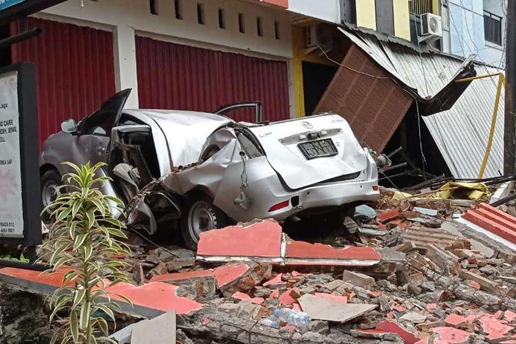Sebuah mobil dan bangunan rusak akibat gempa bumi, di Mamuju, Sulawesi Barat, Jumat (15/1/2021). Petugas BPBD Sulawesi Barat masih mendata jumlah kerusakan dan korban akibat gempa bumi berkekuatan magnitudo 6,2 tersebut.