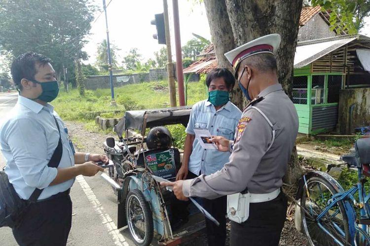 Anggota Satlantas Polres Banjar, Jawa Barar memberikan buku tabungan kepada seorang tukang becak. Tukang becak ini mendapat bantuan sebesar Rp 600 ribu per bulan selama tiga bulan karena terdampak Covid-19.