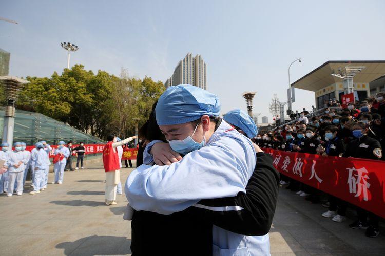 Seorang pekerja medis berpelukan dengan koleganya sesama tim kesehatan dari Jiangsu di Stasiun Kereta Wuhan pada 19 Maret 2020, setelah tim dari Jiangsu meninggalkan kota yang pertama kali melaporkan wabah vurus corona.