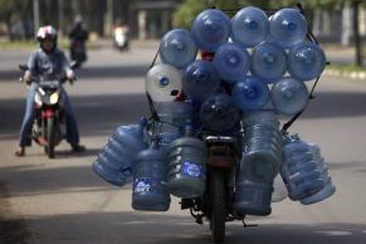 Ilustrasi: Pekerja membawa galon minuman air minum dengan saling diikat di atas sepeda motor di Jalan Raden Inten, Jakarta Timur, Senin (16/1/2012).