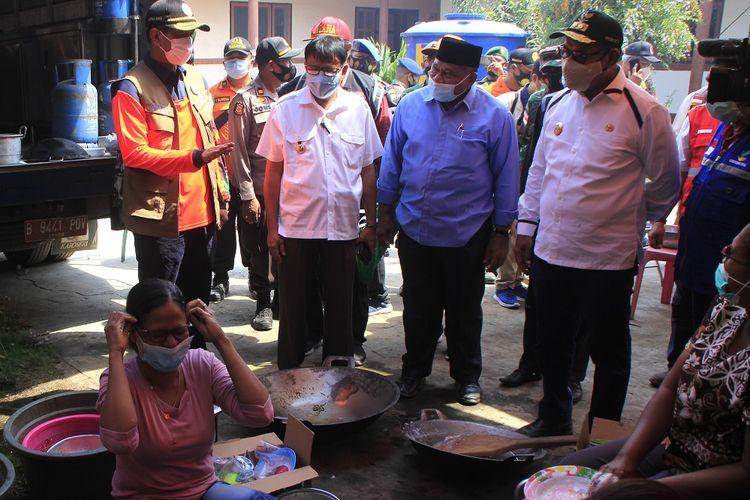 Kepala Badan Nasional Penanggulangan Bencana (BNPB) Doni Munardo (kiri), didampingi Wakil Gubernur NTT Joef Nae Soi (kanan), Bupati Lembata Eliyaser Yentji Sunur (kedua kiri) dan anggota Komisi VIII DPR Ali Taher (kedua kanan) meninjau dapur umum bagi korban erupsi gunung Ili Lewotolok di Kota Lewoleba, Kabupaten Lembata, Rabu (2/12/2020). Kedatangan Doni Munardo ke Lembata dalam rangka memberikan bantuan tanggap darurat senilai Rp1 miliar sekaligus meninjau lokasi pengungsian untuk memastikan penerapannya sesuai dengan protokol kesehatan. ANTARA FOTO/Kornelis Kaha/aww.