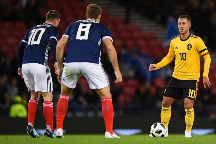 Kapten Timnas Belgia, Eden Hazard, dijaga dua pemain bertahan Skotlandia, Callum McGregor dan Kevin McDonald, pada pertandingan persahabatan di Hampden Park, 7 September 2018.