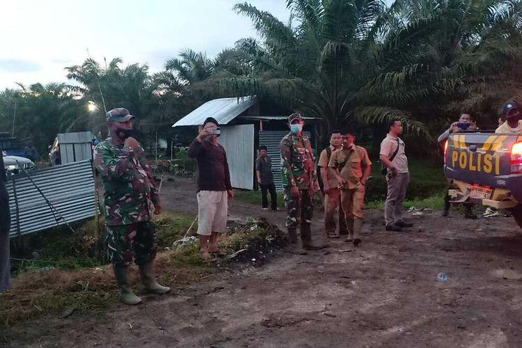Petugas TNI dan kepolisian melakukan pengamanan di lokasi bentrok dua kelompok tani di Desa Sontang, Kecamatan Bonai Darussalam, Kabupaten Rohul, Riau, Selasa (26/1/2021).