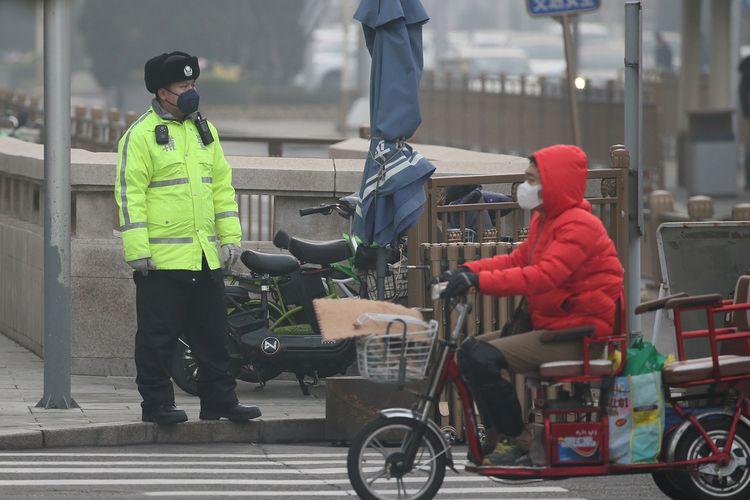 Seorang polsi memperhatikan jalan dengan pengguna melintas di hadapannya di Beijing, China, pada 21 Februari 2020 di tengah merebaknya virus corona.