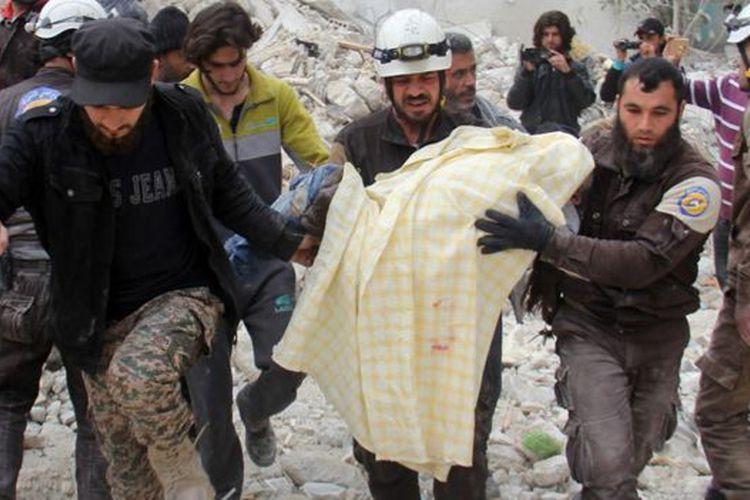 Para petugas membawa jenazah korban serangan dari reruntuhan gedung yang diserang pada Selasa (4/4/2017).