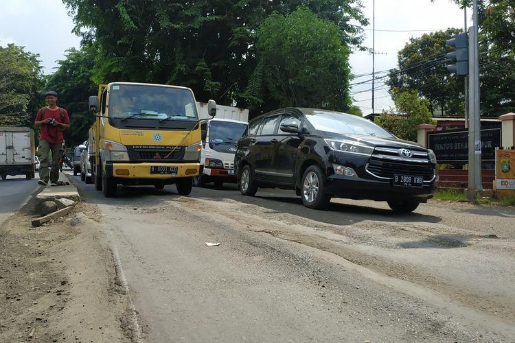 Jalan Raya Siliwangi, Rawalumbu, Kota Bekasi melesak dan bergelombang, menimbulkan perbedaan ketinggian aspal yang rentan mencelakai pemotor di antara truk-truk bertonase besar yang rutin melintas di sana.