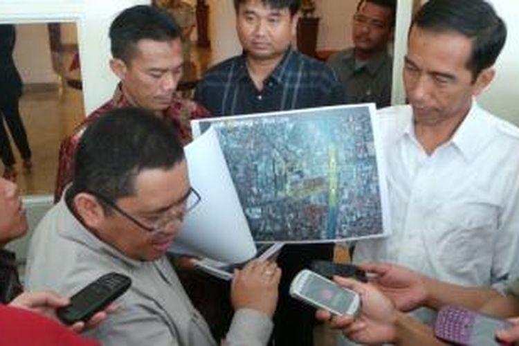 Direktur Teknis PT Jakarta Monorel Rosa Bovananto (kiri) dan Gubernur DKI Jakarta Joko Widodo (kanan) menunjukkan desain shelter monorel kepada wartawan di Balaikota Jakarta, Selasa (26/11/2013).