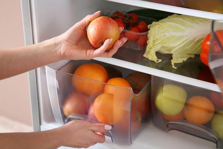 Ilustrasi orang menata buah di kulkas.