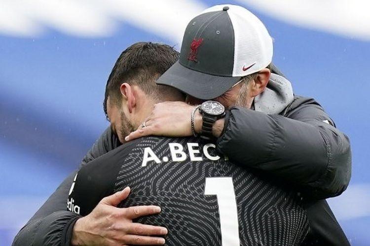Pelatih Liverpool, Juergen Klopp, memeluk Alisson Becker setelah sang kiper mencetak gol kemenangan yang memberikan The Reds tiga poin penuh pada laga kontra West Brom, Minggu (16/5/2021).