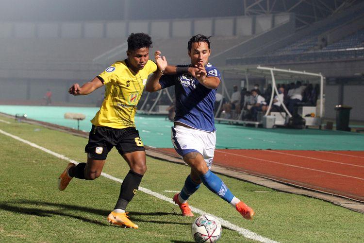 Pemain Persib Bandung Ezra Walian berebut bola dengan pemain Barito Putera Bagas Kaffa pada pekan pertama Liga 1 2021-2022 yang berakhir dengan skor 1-0 di Stadion Indomilk Arena Tangerang, Sabtu (4/9/2021) malam.