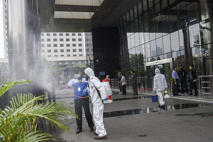 Petugas menyemprotkan cairan disinfektan di halaman Gedung KPK Merah Putih di Jakarta, Rabu (18/3/2020). Untuk mencegah penyebaran COVID-19, KPK melakukan disinfeksi di sejumlah area Gedung Merah Putih.