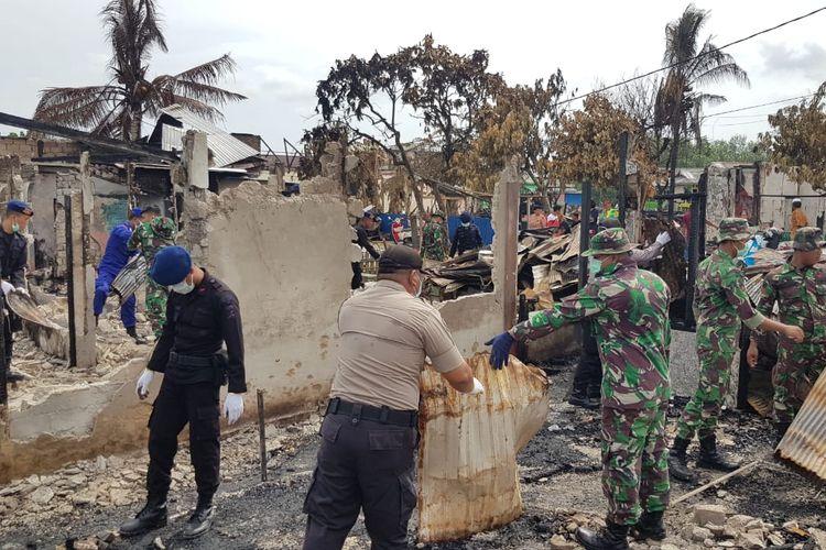 Petugas dari Polda Kaltim dan Kodam Mulawarman membersihkan lokasi setelah massa membakar ratusan bangunan di Pelabuhan Feri Kelurahan Penajam Kabupaten Penajam Paser Utara (PPU), Kamis (17/10/2019).