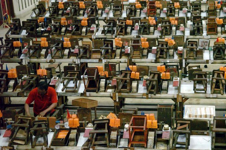 Pekerja membersihkan peralatan linting rokok setelah digunakan buruh linting di unit produksi sigaret keretek tangan di pabrik rokok di Surabaya tahun 2007.