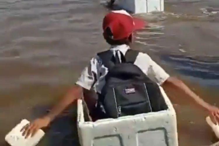 Anak SD di Desa Kuala 12, Kecamatan Tulung Selapan, menggunakan kotak styrofoam bekas untuk menyeberang sungai.