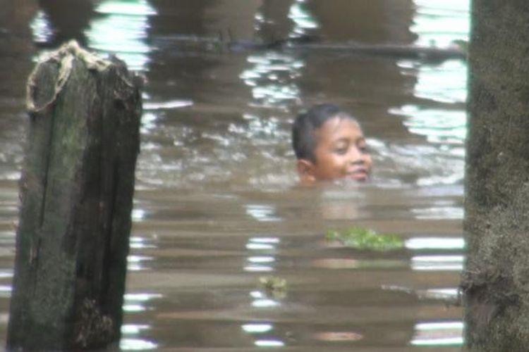Seorang anak bermain di genangan air banjir yang kotor dan pekat  di bawah rumahnya di Desa Gunung Megang Muaraenim