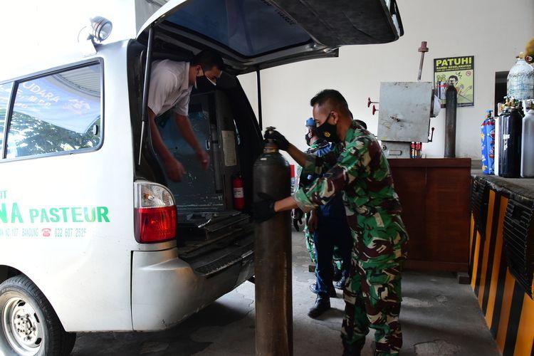 Prajurit TNI AU tengah membantu memasukkan tabung oksigen ke dalam ambulans rumah sakit yang datang ke Lanud Husein Sastranegara, Senin (26/7/2022). TNI AU mengoperasikan Pabrik Zat Asam (Pazam) 731 guna membantu kebutuhan oksigen di rumah sakit dan masyarakat di tengah pandemi Covid-19.