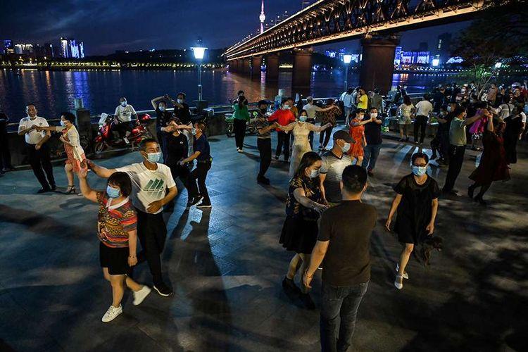 Sejumlah pasangan dengan mengenakan masker menari di sebuah taman di sebelah Sungai Yangtze, Wuhan, Provinsi Hubei, China, Selasa (12/5/2020). Memasuki enam pekan bebas dari lockdown yang diterapkan akibat pandemi Covid-19 sejak Januari lalu, warga Wuhan kembali beraktivitas walau dalam kondisi terbatas.