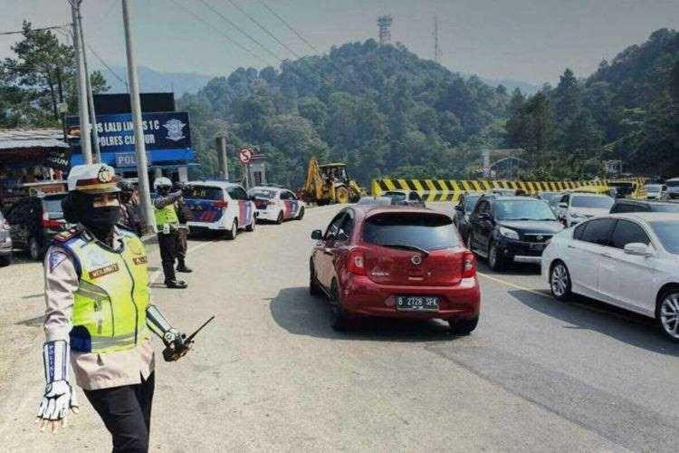 Polisi tengah mengatur arus kendaraan yang memasuki kawasan Puncak Cianjur, Jawa Barat. Sepekan PSBB DKI Jakarta volume kendaraan yang masuk Puncak merosot drastis.