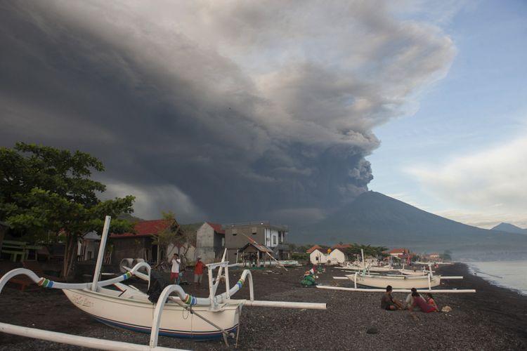 Sejumlah warga menikmati liburan dengan latar belakang Gunung Agung meletus, di Pantai Jemeluk, Karangasem, Bali, Minggu (26/11/2017). Pusat Vulkanologi dan Mitigasi Bencana Geologi menyatakan telah terjadi letusan freatik kedua pada pukul 17.20 Wita yang disusul dengan semburan asap dan abu vulkanis hingga ketinggian 3.000 meter.