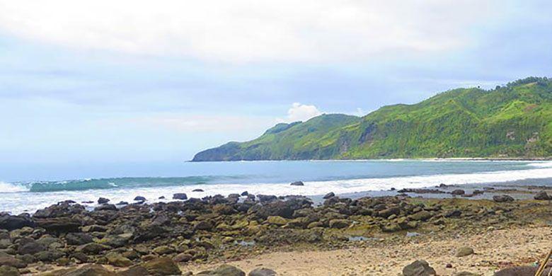 Panorama kawasan pantai nelayan di Menganti dengan tebing perbukitan hijau yang menjorok ke lautan.