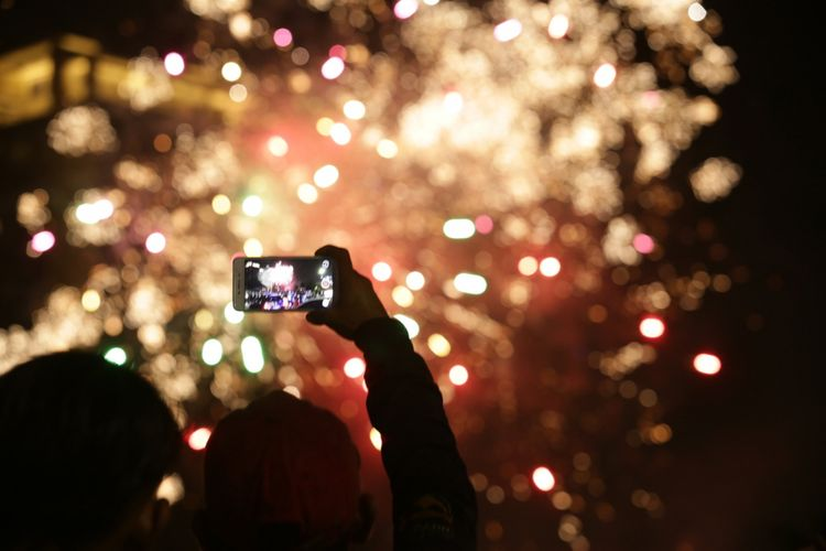 Sejumlah warga mengabadikan pesta kembang api pada malam tahun baru di Kawasan AEON Mall Bumi Serpong Damai (BSD) Tangerang, Banten, Selasa (1/1/2019). Sejumlah warga Tangerang dan sekitarnya memadati kawasan ini untuk merayakan malam pergantian tahun.