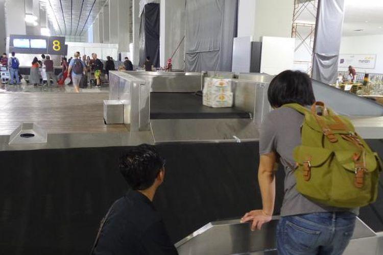 Penumpang menunggu barang mereka di tempat pengambilan bagasi Terminal 3 New Bandara Soekarno-Hatta, Selasa (23/8/2016). Meski pengambilan bagasi sudah cepat, sebagian penumpang masih mengeluhkan minimnya informasi di mana mereka harus mengambil barangnya.