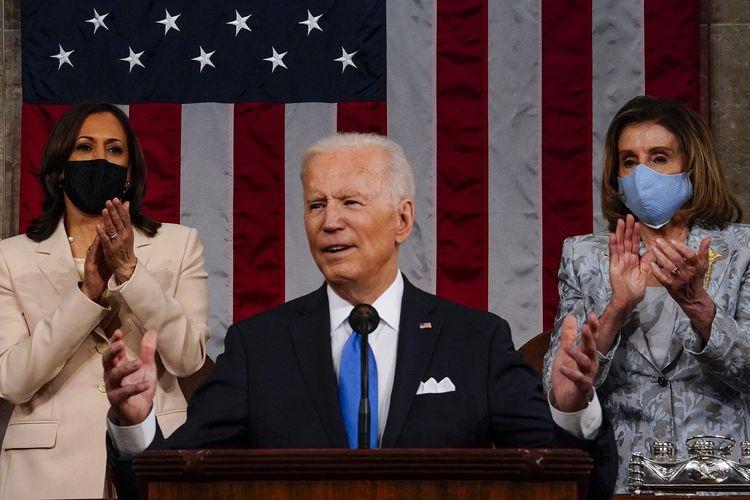 Presiden Amerika Serikat (AS) Joe Biden saat memberikan pidato di depan Kongres di Gedung Capitol, Washington DC, pada 28 April 2021. Berdiri di belakangnya adalah Wakil Presiden Kamala Harris (kiri) dan Ketua House of Representatives Nancy Pelosi.