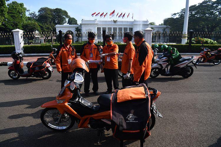 Sejumlah pegawai PT POS Indonesia (Persero) berkoordinasi sebelum pelepasan distribusi bantuan sosial sembako di depan Istana Merdeka, Jakarta, Senin (20/4/2020). Pemerintah mulai menyalurkan bantuan sosial untuk wilayah di DKI Jakarta dalam rangka penanganan COVID-19 di wilayah Jabodetabek.