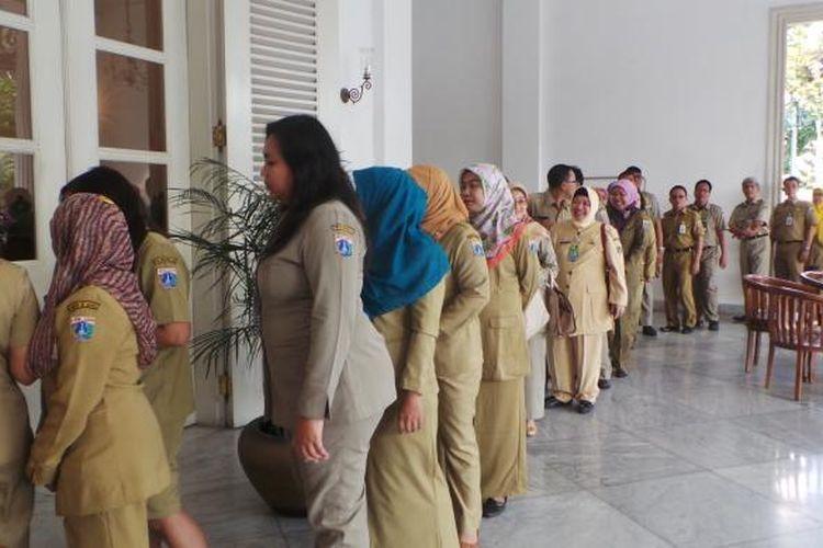 Pegawai Negeri Sipil (PNS) DKI mengantre bersalaman serta bermaaf-maafan dengan Gubernur DKI Jakarta Basuki Tjahaja Purnama pada halal bihalal Hari Raya Idul Fitri 1436 Hijriah, di Balai Kota, Rabu (22/7/2015).