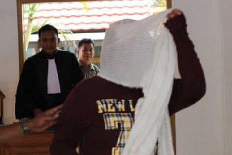 Normayanti berusaha menutupi wajahnay dari bidikan kamera wartawan saat sidang putusan perkara kepemilikan 1910 ekstasi. Normayanti diganjar hukuman penjara 14 tahun.