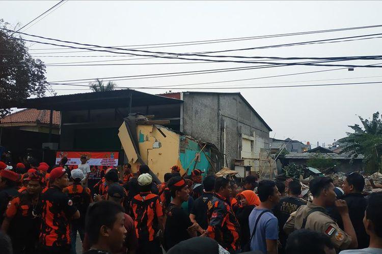 Penggusuran perumahan warga di Jalan Bougenville Raya RT 001 RW 011 Jakasampurna, Bekasi Barat ditunda hingga waktu yang tidak ditentukan, Kamis (25/7/2019). Rumah terakhir yang dibongkar tepat di samping rumah berspanduk salah satu ormas yang dijaga seharian oleh puluhan anggotanya.