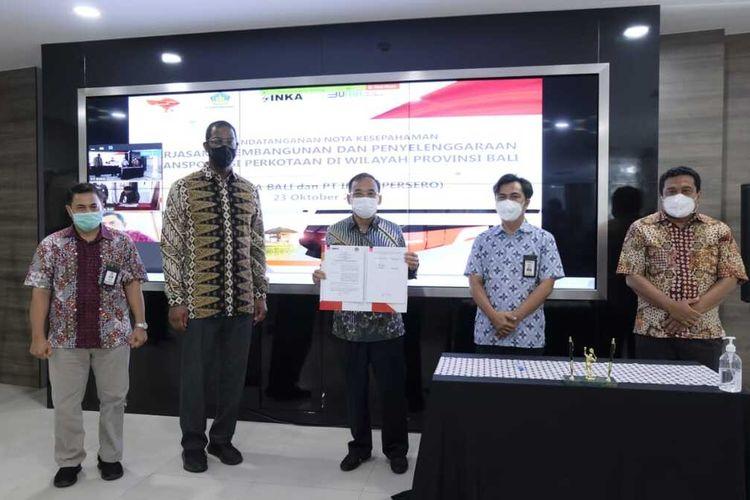 NOTA KESEPAKATAN—Direktur PT INKA, Budi Noviantoro menunjukkan nota kesepahaman kerjasama dengan Perusahaan Daerah (Perusda) Bali untuk pengembangan transportasi listrik berbasis ramah lingkungan di pula dewata, Jumat (23/10/2020)