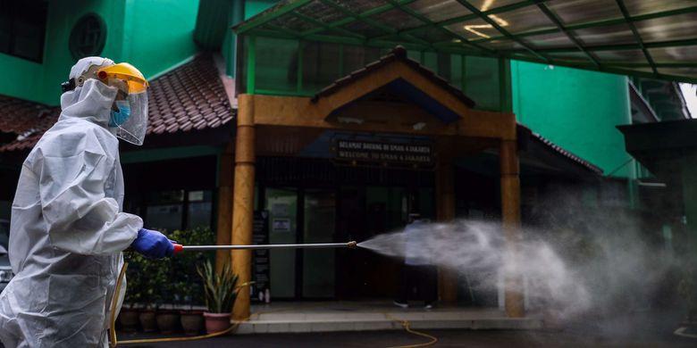 Petugas Palang Merah Indonesia (PMI) Jakarta Pusat menyemprotkan cairan disinfektan di sekolah SMAN 4, Jalan Batu, Gambir, Jakarta Pusat, Selasa (23/6/2020). Palang Merah Indonesia mengencarkan penyemprotan cairan disinfektan di sekolah di tengah masa penerimaan peserta didik baru (PPDB) tahun ajaran 2020/2021.