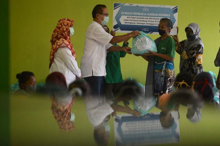 General Manager Corpcomm Kompas Gramedia Saiful Bahri (kiri) menyerahkan bantuan paket bahan pokok dari Yayasan Dana Kemanusiaan Kompas (DKK) kepada buruh gendong di Pasar Giwangan, Yogyakarta, Jumat (15/5/2020).  Bantuan tersebut disalurkan melalui Yayasan Annisa Swasti kepada 434 buruh gendong di Pasar Giwangan, Beringharjo, Kranggan, dan Gamping. Bantuan tersebut diberikan untuk membantu para buruh gendong menjalani kondisi serba terbatas selama pandemi Covid-19.      KOMPAS/FERGANATA INDRA RIATMOKO