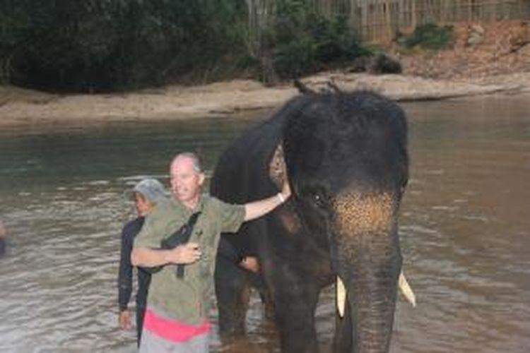 Salah satu peserta Festival Terengganu International Squid Jigging 2014 saat berinteraksi dengan gajah-gajah di Kenyir Elephant Village.