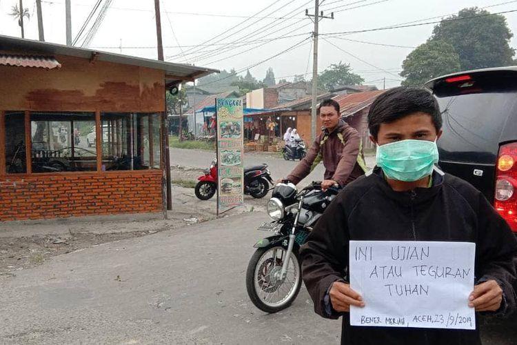 Seorang warga Bener Meriah melakukan sebuah aksi protes terhadap kabut asap yang menyelimuti di Kabupaten Bener Meriah, Aceh, Senin (23/9/2019).