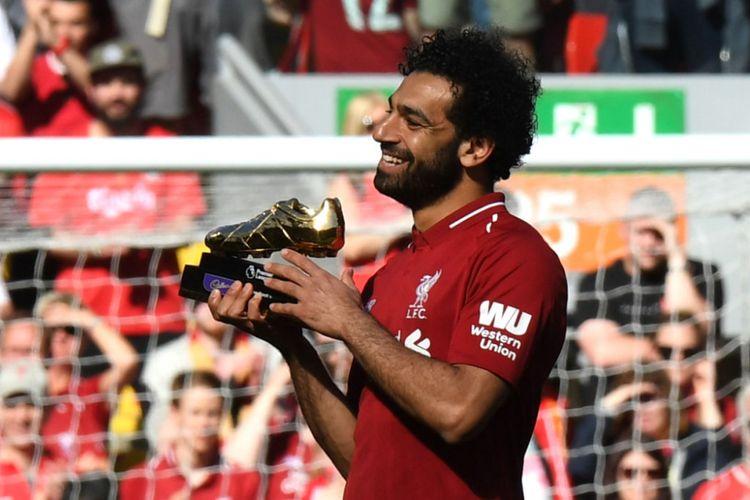 Mohamed Salah memamerkan sepatu emas sebagai simbol pencetak gol terbanyak Premier League seusai laga Liverpool vs Brighton & Hove Albion di Anfield,13 Mei 2018.