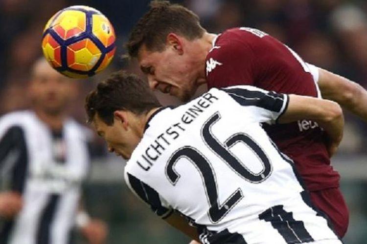Andrea Belotti mengungguli Stephan Lichsteiner dalam duel udara saat Torino berhadapan dengan Juventus di Olimpico Turin, Minggu (11/12/2016).