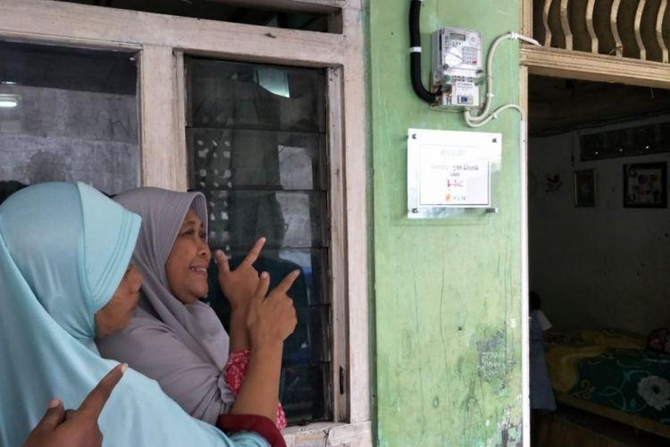 Eni Nurbayeni (kerudung abu-abu), warga Kota Bekasi yang rumahmya disambungkan listrik gratis dari PLN saat tunjukan meteran listrik di rumahnya, Jumat (25/1/2019).