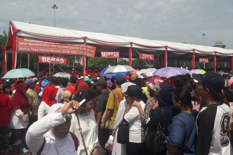 Para warga mengantre sembako dalam acara Untukmu Indonesia di Lapangan Monas, Minggu (28/4/2018).