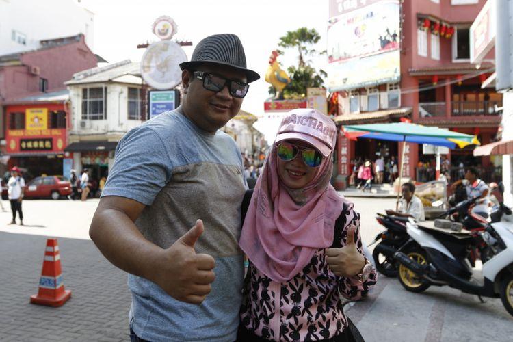 Deni Puguh Darianto berfoto bersama sang isteri saat mengunjungi Jonker Street, Melaka, Malaysia, Sabtu (28/10/2017). Deni bersama isteri menjadi salah satu peserta Federal Oil Goes to Sepang, dan mendapatkan kesempatan menonton langsung MotoGP Sepang.