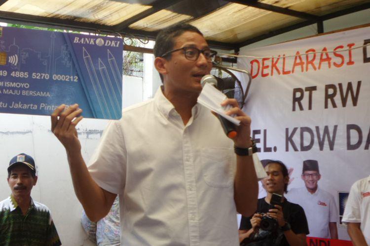 Calon wakil gubernur DKI Jakarta Sandiaga Uno memperlihatkan contoh KJP (Kartu Jakarta Pintar) Plus saat memberi pengarahan kepada relawan di Ciracas, Jakarta Timur, Minggu (26/3/2017).