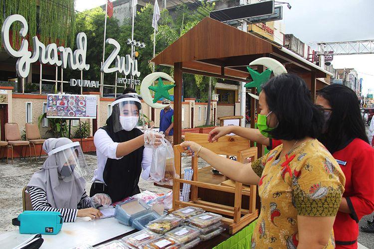 Pekerja hotel melayani pembeli takjil di Kota Dumai, Dumai, Riau, Rabu (13/5/2020). Pengusaha hotel di Kota Dumai memiliki kiat untuk menambah pendapatannya di masa pandemi COVID-19 agar pekerjanya terhindar dari pemutusan hubungan kerja (PHK) dengan cara berjualan takjil dan menu buka puasa selama bulan Ramadhan.