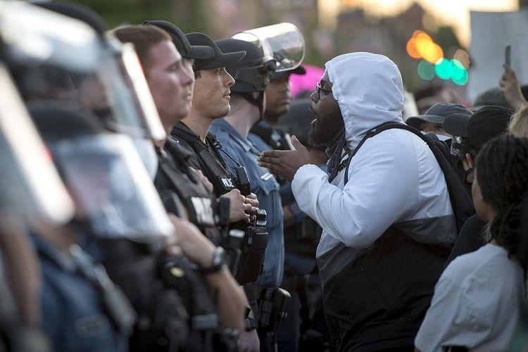 Dalam foto 29 Mei 2020 ini, seorang pengunjuk rasa berhadapan dengan polisi Kota Kansas selama protes atas kematian George Floyd di Country Club Plaza di Kota Kansas.